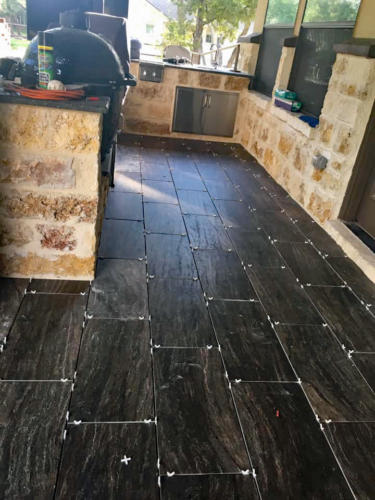 black tile floor install on outdoor patio